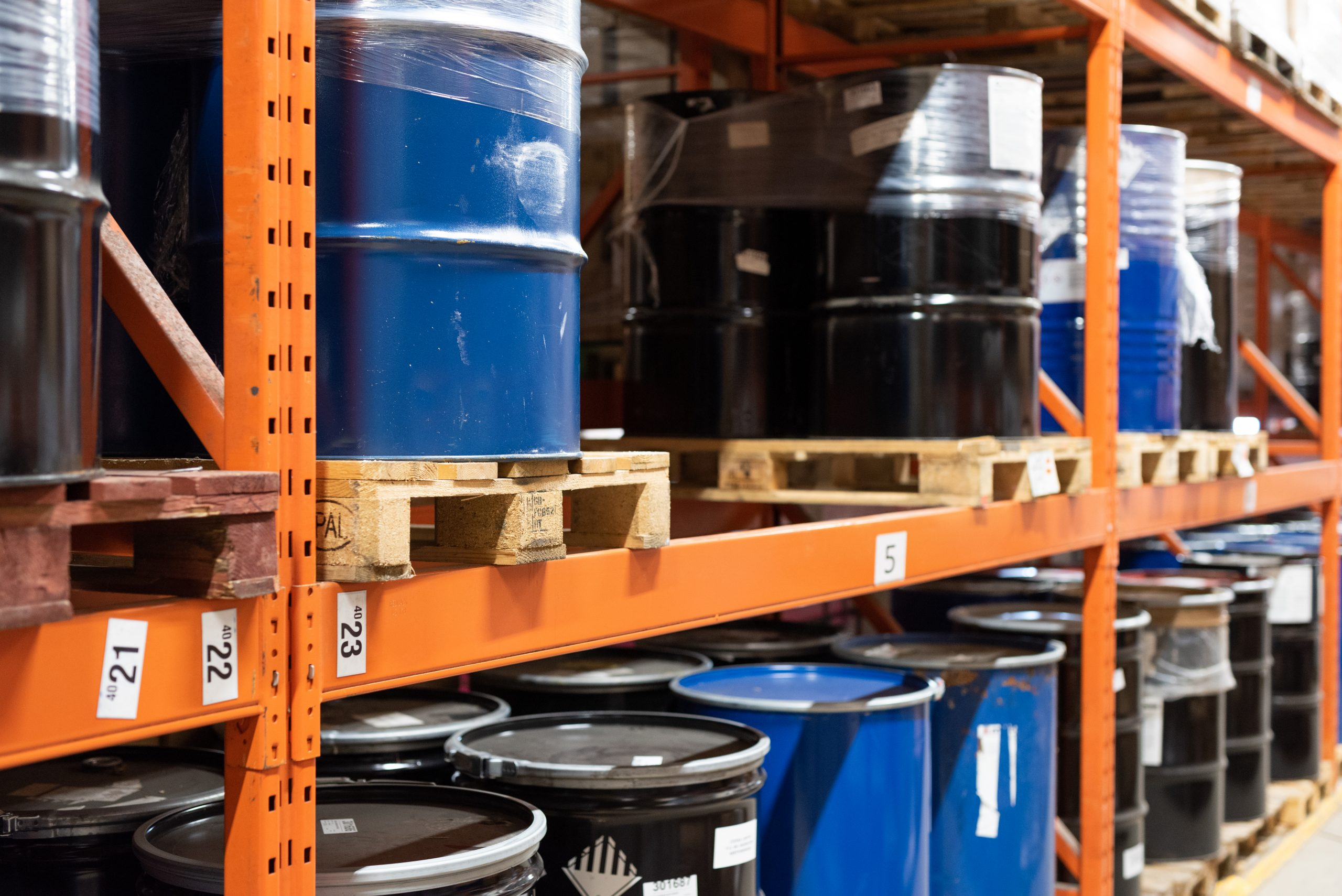 Chemical barrels stacked in a warehouse | Cedesa